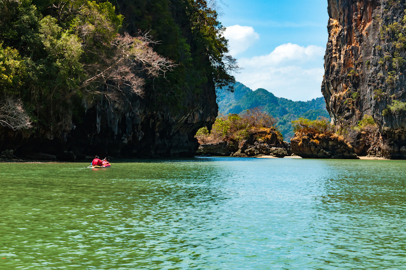 Big limestone rocks and tourists canoeing in Phang nga bay, Thailand
